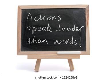 """Actions speak louder than words"" saying written on blackboard over white background"