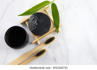 Activated Bamboo charcoal tooth powder on marble background.