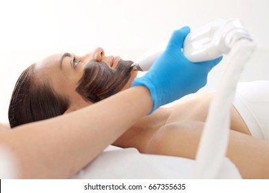 Activated Carbon Mask. Woman in cosmetic surgery during skin care facial treatment.