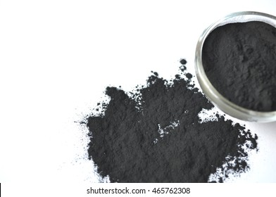 Activated charcoal in a glass bowl and black powder sprinkled around, with copy space. Ingredient for cosmetic face mask and beauty spa treatments.