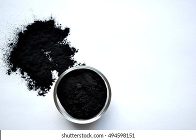 Activated charcoal powder in a glass bowl, close up, top view. Ingredient for cosmetic face mask and beauty spa treatments.