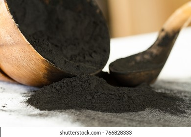 Activated Charcoal Powder Spilling Out of a Wooden Bowl