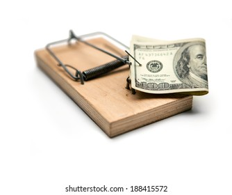 Activated mousetrap with money. Hypothec / studio photography of one hundred dollar bill and mousetrap on a white background