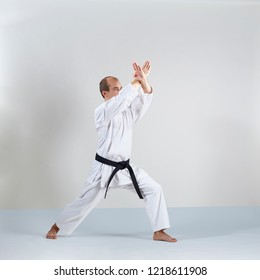 Active adult athlete trains formal karate exercises on gray background