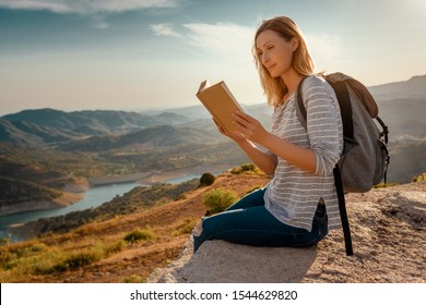 active adventure woman reading a book on top oft the mountain