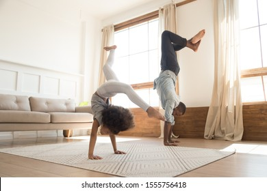 Active african American young father and preschooler daughter stand on hand exercise at home together, overjoyed biracial dad and girl child have fun do morning gymnastics, healthy family concept