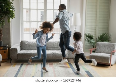 Active african funny dad little son and crazy daughter heavy metal or rock and roll lovers dancing in cozy living room relish life fooling around listening cool music scream with joy enjoy party hard - Shutterstock ID 1687124746