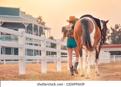 Active Asia cowgirl in hat walking with horse. Farmer girl in countryside ranch. Beautiful woman training and taking care of her horse with love and caring.