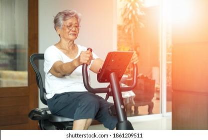 Aktive asiatische Seniorinnen trainieren auf stationärem Fahrrad für gesund im Fitnessstudio zu Hause.
