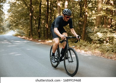 Active bearded man in sport clothing and black helmet riding bicycle  with beautiful nature around. Mature cyclist in mirrored glasses doing favorite hobby outdoors.