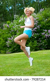 An active beautiful caucasian woman jumping in the park