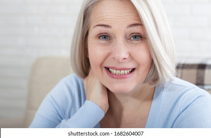 Active beautiful middle-aged woman smiling friendly and looking in camera in living room. Woman's face closeup. Realistic images without retouching with their own imperfections. Selective focus.
