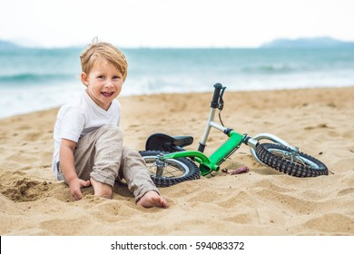 Active blond kid boy driving bicycle in the park near the sea. Toddler child dreaming and having fun on warm summer day. outdoors games for children. Balance bike concept.