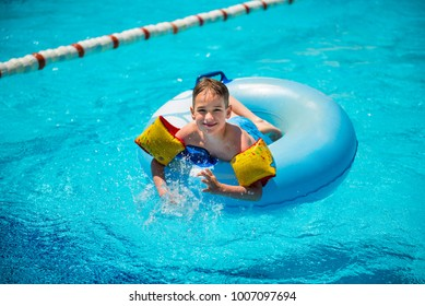 Active boy having fun in the aqua park swimming pool sitting on the inflatable rubber ring.