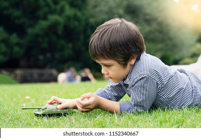 Active boy laying down on the grass playing with soldiers and tank toys in the park, Happy Kid playing wars and peace on his own, Children imagination and development