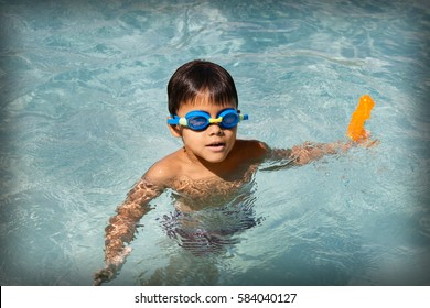 Active boy on summer vacation playing in the pool on sunny day