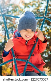 Active boy playing outdoors, 3 Years old kid climbing rope at playground. Happy child in red coat enjoying activity in a climbing adventure park on autumn day