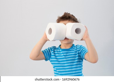 Active boy playing with toilet paper in retro filter,kid boy looking through toilet roll,Child holding two white tissue, Children health care concept