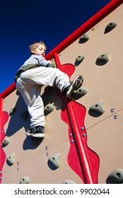 active boy scales a climbing wall