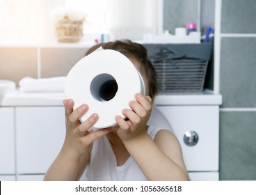 Active boy sitting in the toilet playing with toilet paper,kid boy sitting in the restroom and looking through toilet roll,Child holding two white tissue, Children health care concept