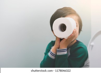 Active boy sitting in the toilet playing with toilet paper in retro filter,kid boy sitting in the restroom and looking through toilet roll,Child holding two white tissue, Children health care concept
