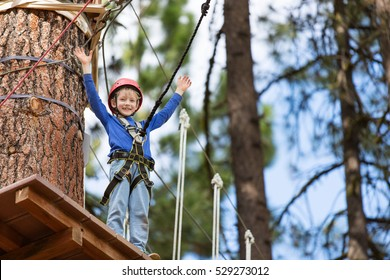 active brave little boy enjoying climbing at treetop adventure park