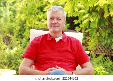 Active casual businessman sitting at home at garden.