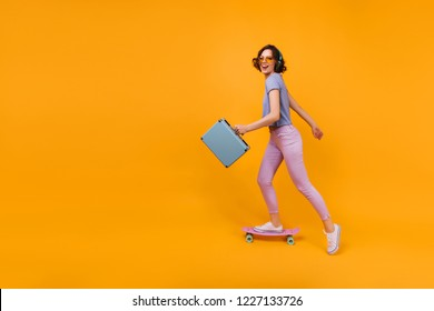 Active caucasian woman with valise skating in studio. Indoor shot of magnificent curly girl standing on longboard on yellow background.