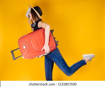 active cheerful girl in a hat goes on holiday with a red suitcase, waits for her flight