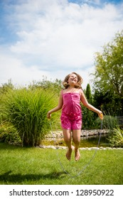 Active child - happy girl jumping with skipping rope outdoor, copy space