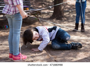 active children games. nice boy gently passes through the tangled rope