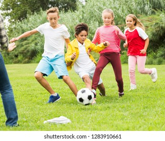active children are jogning and playing football in the park.
