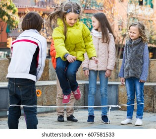 Active children playing rubber band jumping game and laughing outdoors