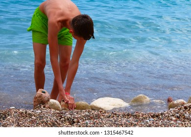 Active children summer vacation at sea. Healthy sunburnt school boy in green shorts is relaxing on sea coast. Sunny summer day.