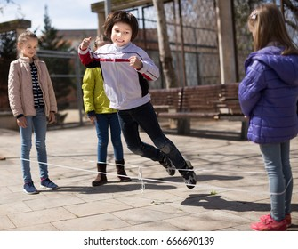 active children's games. Boy jumps over the rope outdoor