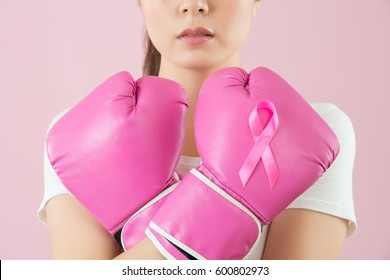 Active Chinese young woman wear boxing gloves crossed arms on the chest to call attention to female cancer disease isolated on pink background. medical and health concept.