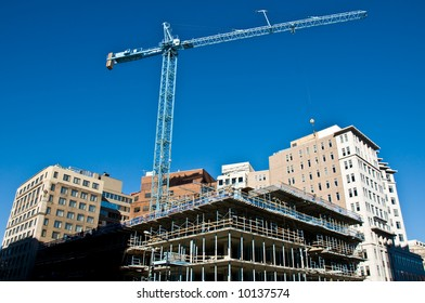 active construction site and crane over a new city building taking shape with a beautiful deep blue sky in the background