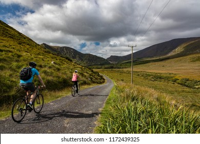 Active couple biking on a rural country road  in the scenic mountain valley landscape of the Dingle peninsula, County Kerry in the Republic of Ireland