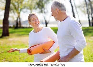 Active couple. Delighted nice woman talking to her husband while going to the training together
