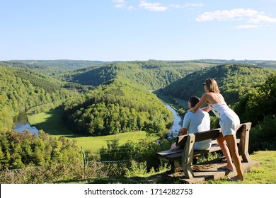 Active couple enjoying forest and river view. Family walking and hiking at famous panoramic point of The Giant's tomb at river Semois in Ardennes nearby the city of Bouillon, Wallonia, Belgium.