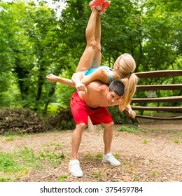 Active couple exercising in nature, back to back lifting