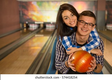 Active couple. Handsome young man smiling holding a bowling ball giving a piggyback to his beautiful cheerful girlfriend at the bowling club copyspace leisure holidays recreation dating relationships