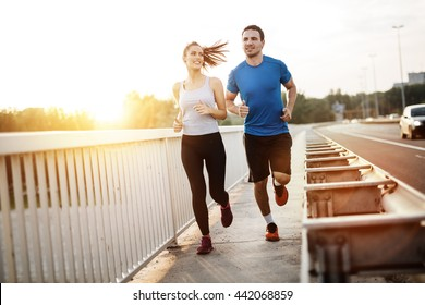 Active couple jogging outdoors during sunset