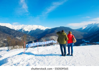 An active couple of people travel to the top peak of mountain, stand and look at beautiful view with snow. Tracks for ski and snowboard sport are near.