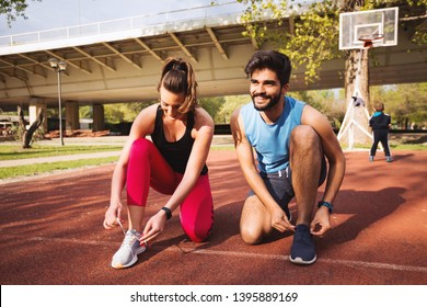 Active couple tying their laces on running shoes