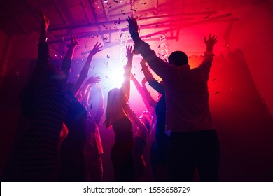 Active. A crowd of people in silhouette raises their hands on dancefloor on neon light background. Night life, club, music, dance, motion, youth. Purple-pink colors and moving girls and boys.