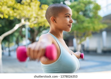 Active curvy woman using dumbbells in the park. Side view of young woman doing stretching exercise using dumbbells. Active athlete working out on fitness routine to lose weight.