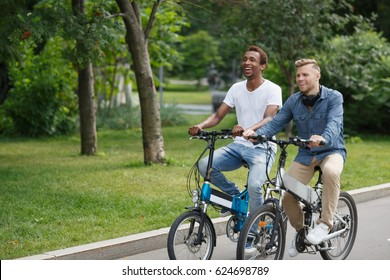 Active day with friend. Two young happy men riding electric bicycles along a road  in green summer park and laughing