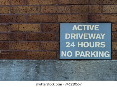 Active driveway 24 hours no parking sign on a building
