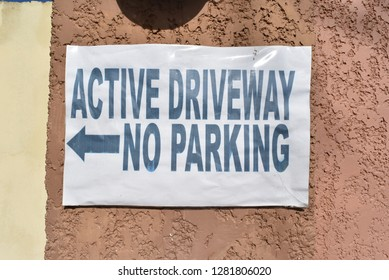 Active driveway no parking sign. Blue text and white background. Posted in a wall with cover.